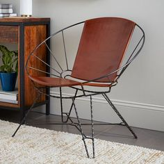 The leather on our Sculpted Metal + Leather Bowl Chair is stretched over an intricate hand-welded metal frame. The frame's sunburst pattern and dramatic silhouette will make this chair a statement piece in any room.