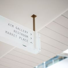 Overhead directional signage in frosted glass, with copper coloured metal…