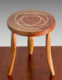 Three Leg Stool with off set turned legs in Paperbark with bronze powder filled epoxy on the seat. The wood for the seat is probably Jarrah. By John MacFadyen