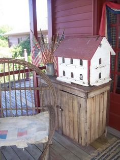 Rustic Country Porch...twig chair with worn old quilt...wood cupboard with distressed birdhouse...flags.