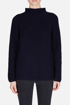 """The fall 2015 Lemaire collection is a study in more and less. """"More dangerous, less melancholic,"""" is how Christophe Lemaire describes the pieces and the woman who wears them. This ribbed sweater is made from deep blue wool that is just a notch above navy. The wide, high neck provides warmth without the restrictive feel of a typical turtleneck. Subtle patterns at the décolletage suggest—ever so slightly—what lies beneath."""