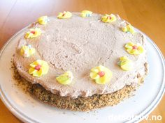 """""""Påskens kaffekoskake"""" er en enkel og deilig kake basert på hasselnøtter og sjokolade. Kakebunnen består av bare fire ingredienser og er veldig rask å bake. Dessuten er den uten hvetemel og passer derfor for allergikere. """"Påskens kaffekoskake"""" dekkes med luftig sjokoladekrem som får mild sjokoladesmak av sjokolademelkpulver. Populært hos små og store! Pynt med gul kakepynt for å få påskestemning!"""