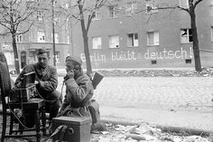 """Soviet Army soldiers operate a military field telephone during the final throes of the Battle of Berlin. Behind them, a defiant German has painted the slogan""""Berlin remains German!"""" on a building wall. A Soviet soldier has interrupted the phrase with a painted hammer and sickle before the word """"Deutsch"""". Berlin, Germany. 2 May 1945."""