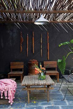 Patio rústico con parasol de madera y muebles encontrados en la casa de dos diseñadores.