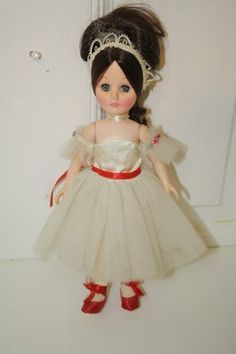 "1975 Effanbee ballerina in white dress with red trim. #1476 still with hair net (hair net torn a little). Green eyes with black hair Measures approx: 12"" $30"
