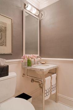 White marble washstand in a powder bath. Herringbone pattern on the floor.