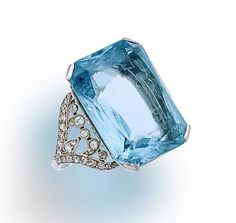A belle époque aquamarine and diamond ring, circa 1910 set with a rectangular-cut aquamarine, within a scrolling openwork old-cut diamond gallery and shoulders; aquamarine weighing approximately: 19.60 carats; estimated total diamond weight: 1.20 carats; mounted in platinum