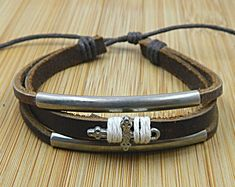 personalized omens mens fancy leather dark brown  bracelet with metal pipe and cross  wristband. $7.99, via Etsy.