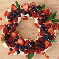 Berry Christmas Pavlova Wreath What you need: For Pavlova Mixture Egg Whites - 5 Caster Sugar - 1 Cup Cornflour - 1 tbsp Vanilla Essence - 1 tbsp Pavlova Toppings Cream - Blueberries - 1 punnet Strawberries - 2 punnet Raspberries - 1 pun Christmas Pavlova, Christmas Deserts, Christmas Party Food, Xmas Food, Christmas Appetizers, Christmas Cooking, Holiday Desserts, Christmas Treats, Holiday Recipes