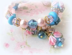 Watch out Spring, here I come! Lovely memory bracelet on stainless steel wire. Exquisite artisan floral glass lampwork beads in cheery spring colors! SW crystals and pearls, GP ball head pins, and other designer quality components. Soon to be listed in my Etsy shop at www.VRBBoutique.etsy.com