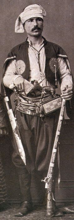 """Ottoman from  Trebizond, wearing a large kama sword and holding a rifle. From:Les costumes populaires de la Turquie en 1873, 74 photographic plates by Pascal Sebah, published by the Imperial Ottoman Commission for the """"Exposition Universelle"""" of Vienna in 1873."""