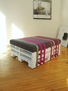 Create an easy-to-assemble ottoman with a couple of sturdy pallets, a few colorful ribbons and a nice cushion.