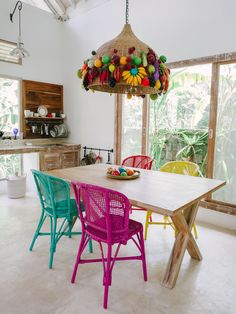 Colourful chairs and quirky pendant decorated with artificial fruits