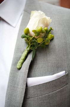 The groom's boutonniere pairs a single white rose with hypernicum berries.