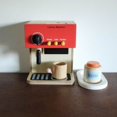 Great espresso machine made out of wood with accessories. By pressing one of the buttons white or brown beads will fall out. ( depending on which one fills ) into the cup. Making coffee is a true ex