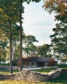 Note the fence - The cottage, designed by Earl Young, relies heavily on stone quarried in northern Michigan. The Radandts restored the distinctive fence and added new ones close to the house as a way of extending the architecture into the landscape.
