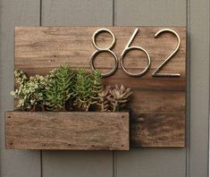 This house number planter box makes the perfect addition to any front porch. We start by staining poplar wood a Dark Walnut color and seal it well with a water based, satin finish polyurethane. Three holes are drilled into the bottom of the planter box section to provide proper drainage for your plants. This planter can be made with or without the metal numbers. We provide eye hooks for mounting your planter. Succulent plants are not included. The overall measurement of this planter is 18…