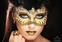 Topaz gems accent an artistic golden masquerade make-up mask.