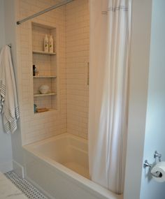 Large tile shower shelves at end of bathtub. Subway tile.