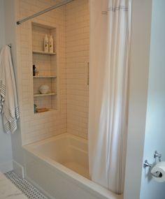 Large tile shower shelves at end of bathtub. Subway tile.