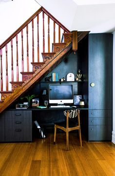Office under the stairs. Paint walls and cabinets black so they recede to background. Creative storage solutions for small spaces.