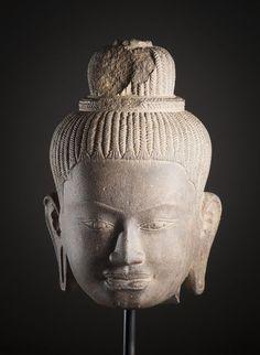 Tête de divinité féminine. Cambodge, Art Khmer, style du Ba Phuon, Xième s. Grès gris et dense, présentant de belles cicatrisations et une patine ancienne.