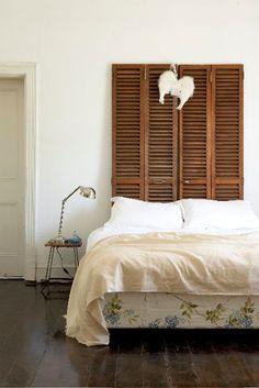 Cabecero de madera reciclado. Unas puertas de persiana hacen el papel.