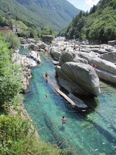 The magical jade green waters of the Verzasca river flow peacefully over smooth polished rocks, passing under the picturesque double arches of the Ponte dei Salti in Lavertezzo.
