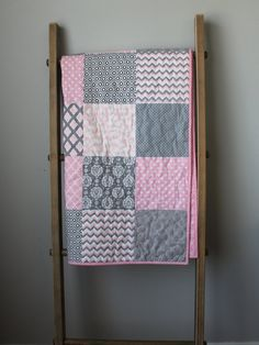 This modern baby girl quilt is made using a soothing, classic color palette of pale pink, grey, and white. Prints of damask, chevron, dots, and
