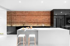 Glossy black cabinets, exposed brick, and a white island