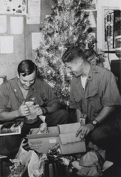 """1968 - Christmas in Vietnam: Marine Corporals John J. Risenbarth, left (Reno, Nevada) and Stephen B. Milistef (Hayward, California) of Marine Heavy Helicopter Squadron 462 [HMH-462], Phu Bai, open presents from home Christmas morning in the crew's lounge (official USMC photo by Staff Sergeant Bill Graham)."""""""