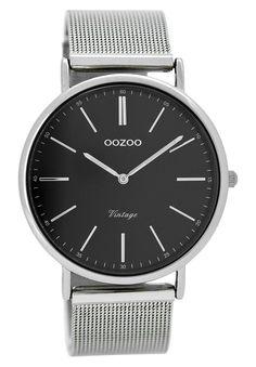 OOZOO Horloge Vintage 40 mm C8815. Trendy en populair dameshorloge met stalen, zilverkleurige kast. Het horloge heeft een zwarte wijzerplaat zilverkleurige index en wijzers. De zilverkleurige, stalen mesh (milanese) horlogeband sluit door middel van een klepsluiting. De doorsnee van de kast is 40 mm. Trendy en elegant model uit de OOZOO vintage-collectie.