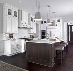 brown and white kitchen designs. Three Lily Hanging Shades hang above curved white marble countertops  seating three gray leather counter stools in front of a dark brown kitchen island White and features shaker cabinets paired with