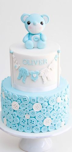 Buttons and sweet little baby outfits hanging on a line - absolutely adorable! But what makes this cake standout is the big teddy bear cake topper adorning it! Torta Baby Shower, Baby Shower Cakes For Boys, Baby Boy Shower, Baby Shower Cupcake Toppers, Pretty Cakes, Cute Cakes, Beautiful Cakes, Fondant Cakes, Cupcake Cakes