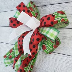 Summertime is almost here and this fun bow would make a great decoration for your mailbox, wreath, swag, or porch rail! Use it to help decorate for a summer bash by the pool or bring it indoors and use it on a beautiful vase in your kitchen! The possibilities are endless! #SummerBow #WatermelonDecor #WinniesCraftyWorld Watermelon Decor, Summer Bash, Indoor Wreath, Artificial Silk Flowers, Red Ribbon, Summer Wreath, How To Make Bows, Green Stripes, Deco Mesh