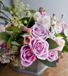 delicate pink and peach roses, decorative maple, dill weed, jade flower, rich plum colored wild geraniums and cyclamens make up this lovely bunch