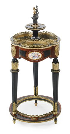 ♔ ATTRIBUTED TO CHARLES-GUILLAUME DIEHL 1811- CIRCA 1885 A NAPOLEON III GILT AND PATINATED BRONZE MOUNTED BURR AMBONYA AND EBONIZED JARDINIERE PARIS, CIRCA 1870'S SURMOUNTED BY A GILT BRONZE FEMALE FIGURE, THE SIX-LOBED TOP INSET WITH THREE PLANTERS INTERSPACED WITH GILT BRONZE GRASSHOPPERS, THE FRIEZE MOUNTED WITH THREE PORCELAIN PLAQUES.
