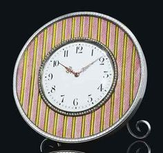 A SILVER AND GUILLOCHÉ ENAMEL DESK CLOCK BY FABERGÉ, WORKMASTER'S MARK OF HENRIK WIGSTRÖM, ST PETERSBURG, 1908-1917 Circular, enameled with bands of salmon pink and yellow over a moiré guilloché ground, centring a white dial with black Arabic chapters and pierced gold hands, within a seed-pearl bezel, all within a laurel-chased border. Provenance: H.M. Queen Alexandra of England, purchased from Fabergé, London on 27 May 1909 for £38, thence to Queen Victoria Eugenia of Spain.