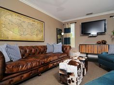 A classic leather Chesterfield sofa takes center stage in this masculine living room. Blue and white throw pillows add color to the sofa, while cowhide ottomans complement the warm leather and provide a place to rest your feet.