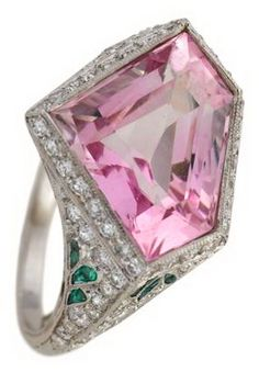 Art Deco platinum and diamond, morganite ring   Unusual kite shaped morganite millegrain bezel set, round cut diamond surround; pave diamond set shoulders with caliber cut emerald 'leaf' accented on either side, platinum filigree basket.