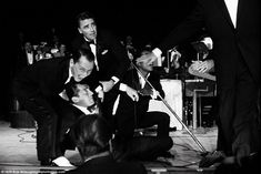 Sinatra, Lawford, Dean Martin and Davis Jr. having some fun during a live performance in 1...