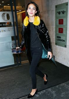 Alexa Chung wears a sweater, skinny jeans, a rain slicker jacket with a fur collar and pointed-toe heels