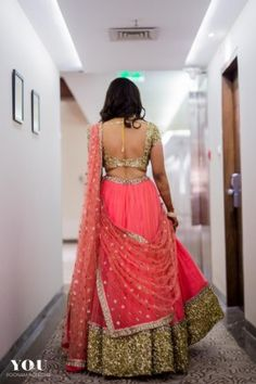 Engagement Lehenga - Bride in a Coral Lehenga with Golden Detailing and Net Dupatta  #wedmegood #indianbride #indianwedding #bridallehenga #lehenga #corallehenga #goldendetailing #backlessblouse #gold #netdupatta