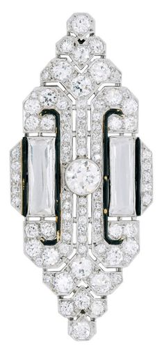 An Art Deco Rock Crystal, Enamel and Diamond Brooch, circa 1920. The navette-shaped plaque centering a round diamond collet flanked by a pair of rectangular rock crystals and accents of black enamel, within a ground of round diamonds, mounted in platinum, French assay marks. #ArtDeco