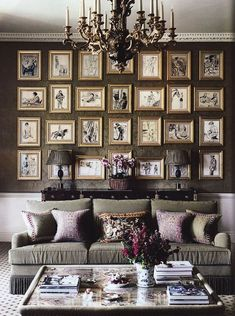 Cosy living room with a wall entirely covered by gold framed art prints #pictures #interiordesign - More wonders at www.francescocatalano.it