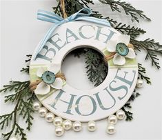 """Beach Christmas life preserver ornament with """"Beach House"""". This wooden life ring makes a perfect ornament for your coastal home!  Wood base is rustically painted with the sentiment """"Beach House"""", a couple clusters of white arks and aqua limpets, and a rustic jute hanger is all it takes to add instant coastal and nautical charm! I also add a cute blue/white bow for the top. Great coastal colors make this a perfect gift for any beach lover!!  4.75"""" diameter."""