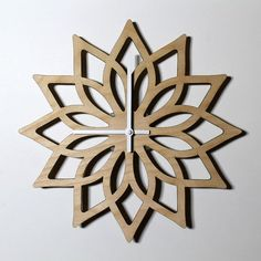 Matte brown and natural finishes shown. A modern, minimal Lotus design wall clock. Made from laser cut birch plywood. Available in natural with a