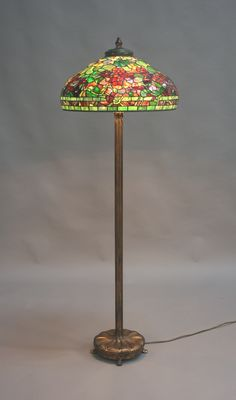 Tiffany Studios floor lamp at Toovey's Auctioneers  To be offered as part of our three-day auction of Antiques, Fine Art & Collectors' Items in our sale of British and Continental Ceramics and Glass. A Tiffany Studios Nasturtium pattern green and brown patinated domed leaded glass shade and matched gilt bronze floor lamp, circa 1910, the column base with relief stem detail emanating from the circular foot with stylized onion moulded decoration, raised on four scroll feet, estimate…