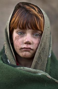 Afghan refugee girl, laiba Hazrat, 6, poses for a picture, while playing with other children in a slum on the outskirts of Is...