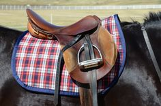 """Beautiful red, white and blue Tartan Saddle Pad.  Professionally made with the highest quality products.  Rugged Tartan fabric, breathable 400g fill and lined with a rugged wool that will wear like iron, yet have the feel of absolute luxury.  Pre-washed with no concern of shrinking or bunching.  23"""" spine, easily fits dressage and cross country saddles up to 18"""".  Shown with an 18"""" saddle.    Machine wash cold and line dry."""